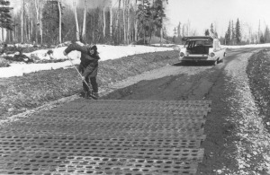 Photo courtesy of Jane Fair. Jane Fair works to repair the gravel road around the steel airplane mats that the Fairs had placed to reinforce a soft spot. Such repairs and stabilization techniques were typical of early homestead roads.