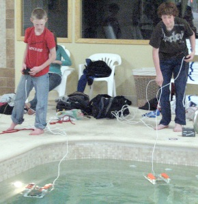 Photo by Jenny Neyman, Redoubt Reporter. Austin Frederick, left, and Nathan Zorbas, seventh-graders in Allan Miller's robotics class at Kenai Middle School, pilot their SEAPerch submersible crafts in the King's Inn pool Friday. The class built the aquatic robots from scratch.