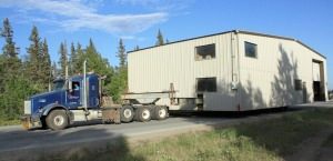 Photo by Patrice Kohl, Redoubt Reporter. A semi hauls a shop belonging to Tina and Erik Barnes up the Kenai Spur Highway on Monday. The shop had to be moved due to bluff erosion.