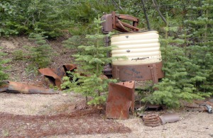 An abandoned washing machine, bed springs, and various other gold rush artifacts sit at the shore of Lake Bennett.
