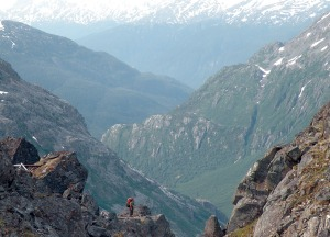 Photos by Jenny Neyman, Redoubt Reporter. Jen Dulz, of Wasilla, stands on a ledge just below the summit of Chilkoot Pass on July 8, looking back at the twisting valley she just climbed.