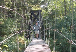 David Greenockle, of Philadelphia, crosses a suspension bridge July 7 on the lower portion of the trail, before it climbs out of the Southeast Alaska rainforest.