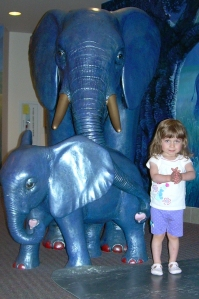 Photo courtesy of www.caringbridge.com. Emily Grace Jacobs, 2, poses in front of the elephants at Children's Hospital in Seattle in May, where she was diagnosed with Chiari malformation of the brain.