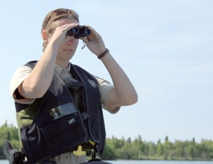 Photos by Patrice Kohl, Redoubt Reporter. Alaska State Parks ranger Ali Eskelin watches fishing boats from afar for signs of potential illegal activity on the Kenai River.