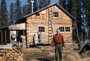 Photo courtesy of the Kenai Peninsula College Anthropology Lab. One of Soldotna's earliest residents, Howard Binkley, poses in front of his new cabin in 1952.