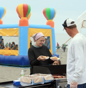 Photo by Patrice Kohl, Redoubt Reporter. Cindy Ward, of Palmer, accepts two hot dogs from a Baptist volunteer, while children bounce behind her in a bounce house the volunteers erected to entertain children.