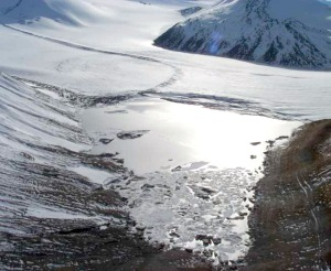 Photo by Lyman Nichols, NOAA. An ice-dammed lake is seen at the head of Skilak Glacier in 2002, with the glacier extending down the valley to the right. The lake fills with runoff water and drains every two to three years, raising water levels in the lower Kenai River.