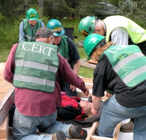 "Photo by Jenny Neyman, Redoubt Reporter. CERT team members extract a ""victim,"" Cindy Moore, during an earthquake scenario training drill Saturday in Kenai. CERT members, clockwise from bottom left, are Steve Lewis, Tom Burg, Eric Boehmler, Victor Hett and Kathy Heindl."