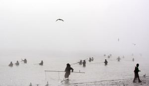 Photo by Patrice Kohl, Redoubt Reporter. Alaskans fishing the opening weekend of the Kenai River dipnet fishery in July, stand silhouetted against a haze of smoke that blew into the area due to a wildfire burning on the Kenai Wildlife Refuge. Some believe this year's Kenai River dipnet fishery may have been the biggest one yet.