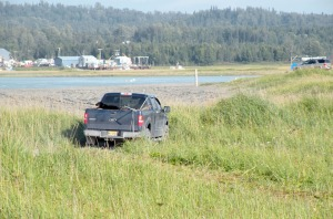 Photo by Jenny Neyman, Redoubt Reporter. A truck carrying dipnetters drives over fragile beach grass covering ecologically important dunes at the Kasilof River mouth Aug. 6. The fragile grass suffers abuse each summer, despite signs asking people to stay off it.