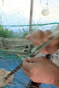 Brian Mahan moves a mending needle swiftly as he repairs a hole in a setnet earlier this summer.