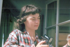 Photo courtesy of KPC Anthropology Lab. Soldotna's first librarian, Joyce Carver, seen here using a hand-viewer to examine some color slides, was honored posthumously in 1972 when the city's current library was named in her memory.