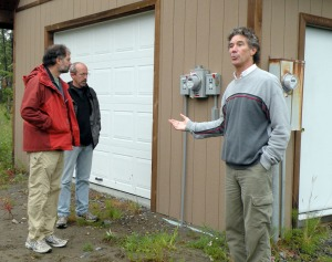 Photo by Jenny Neyman, Redoubt Reporter. Philip St. John, right, leads the Alaska Solar Tour at a home in Kasilof on Saturday, while Phil North, left, and Dan Chay examine a power meter hooked up to solar panels.