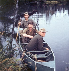Photo courtesy of Peggy Arness. Jimmy Petersen, with a rifle in the middle of the canoe, is accompanied by his boss,  Kenai National Wildlife Refuge Manager Dave Spencer (back of the boat), and an unidentified man. Petersen Lake was named for him.