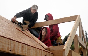 Photo by Jenny Neyman, Redoubt Reporter. Tim Wight and Skyview High School students Mary Doremire and Heath Healy work Thursday on the roof of a shed that the school's new building trades class is working on.