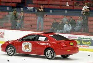 Photo by Jenny Neyman, Redoubt Reporter. Hockey fans at a recent Kenai River Brown Bears game try to throw hockey pucks into the open sunroof of a Saturn Coupe donated by Magnum Motors.