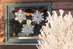 Cutout snowflakes hanging in the window of the Kenai Chamber of Commerce cabin have nothing on the beauty of the hoar frost coating a bush just outside the window.