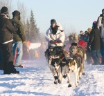 Jim Lanier, of Chugiak, and his dog team leave the crowded confines of the starting chute.