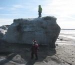 Sammy Anders stands atop a chunk of ice on the beach in Kenai on March 30, with Eliza Anders drawled by the formation. By Nadia Anders, Nikiski