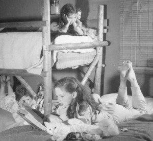 Photo by Bob and Ira Spring. Martha Lancashire reads to her sisters at bedtime.
