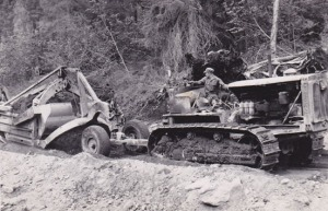 This photo of catskinner Red Jaynes was taken somewhere on the Kenai Peninsula. He's using a tracked vehicle to tow a carry-all to a construction site during work on the Sterling Highway project.