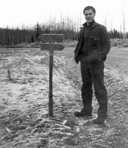 "Photo courtesy of Al Hershberger. The ""Y"" junction in Soldotna was a little less obvious in its early days. Here, ARC engineer Louie Hendricks poses next to a directional sign indicating which way to turn for either Kenai or Moose Pass."