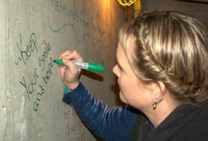 Photos by Jenny Neyman, Redoubt Reporter. Meggean Bos, a volunteer at Central Peninsula Hospital, writes a message Saturday on the wall of a concrete vault that will hold the accelerator in the new radiation oncology clinic under construction at Central Peninsula Hospital.