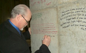 Dr. John Halligan signs a wall of the concrete vault that will hold the accelerator at the new radiation oncology clinic under construction at Central Peninsula Hospital, as part of the Written in Stone project.