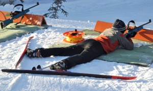 After skiing a quick loop, Gabe Bruno, still with skis on, assumes a prone position and takes aim on a target.