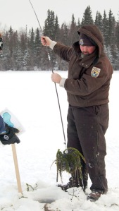 Toby Burke pulls up a brush that snagged elodea beneath the ice.