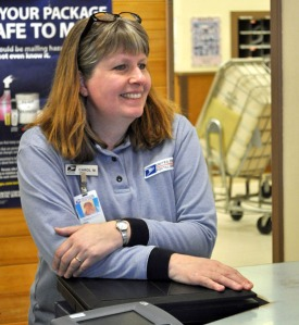 Photo by Joseph Robertia, Redoubt Reporter. U.S. Postal Service clerk Carol Marsh chats with a customer at the Kasilof Post Office on Friday. For nearly 30 years Kasilof residents have been greeted by her smiling face, but she will soon be retiring from USPS work.