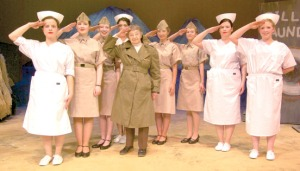 """Mary Quesnel, of Kenai, who served in the Army Nurse Corps in the South Pacific during World War II, poses with actresses portraying nurses in the Kenai Performers musical """"South Pacific,"""" set in World War II. Quesnel wears her field jacket from her time of service, while the characters wear costumes that are, """"Made to look nice. Ours were made more for the weather,"""" Quesnel said."""