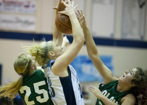 Colony's Audrey Michaleson, left, and Sarah Brumbaugh, right, battle Soldotna's Katelynn Kerkvliet, center, for the rebound during a Saturday game at the 2013 Northern Lights Conference Tournament in Soldotna.