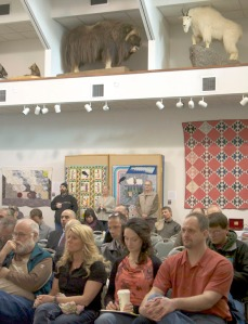 The public listens to the proceedings under taxidermy displays at the Kenai Chamber and Visitors Center.