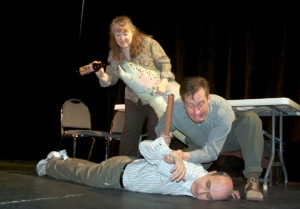 """Photo by Jenny Neyman, Redoubt Reporter. Mrs. Peacock (Terri Burdick) and Professor Plum (Randy Daly) check Mr. Boddy (Joe Rizzo) for signs of life in a rehearsal of Triumvirate Theatre's movie parody """"Clue,"""" to be performed this weekend at Mykel's."""