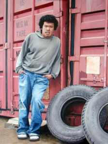"""Travis"" shows a young man leaning against Conex containers with tires in the foreground, by Adcox."