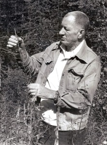 Photo by Clark Fair, Redoubt Reporter. Longtime Kenai Peninsula College instructor Boyd Shaffer examines a stand of fireweed during a class in 1985.