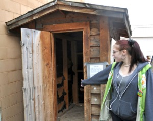 Photo by Joseph Robertia, Redoubt Reporter. Megan Middleton looks in one of the night donation areas behind the Bishop's Attic thrift store in Soldotna. Theft of their donations has been a problem.