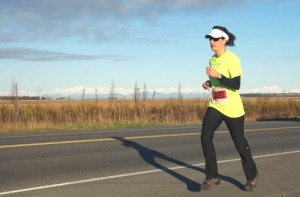 File photo by Jenny Neyman, Redoubt Reporter. A runner in the Kenai River Marathon heads down Bridge Access Road with the mountains flanking Cook Inlet behind her.