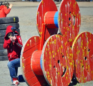 A player returns fire from behind a barricade of large wooden spools that serve as cover from fire, as evidenced by the paint splattered all over them.