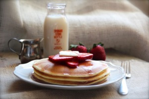 Photo courtesy of Alaska from Scratch. Evoy has amassed a collection of fabrics, antique silverware, milk bottles and other props to use for her food photography. Seen here are  ricotta pancakes with strawberry maple syrup.