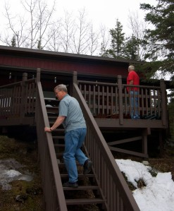 Photo by Jenny Neyman, Redoubt Reporter. Harpring, on stairs, and Mushovic look over repairs made since the tree smashed the deck and punctured the roof in 2011. Repairs had to wait over a weekend, though, because the tree blew down on a Friday after business hours and the Kenai River Center wasn't open to issue the necessary permit to remove the tree —since it fell within the anadromous habitat protection zone — until the following Monday.