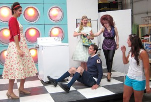 "Photos by Ray Lee, Redoubt Reporter. The cast of ""Suds"" — from left, Elan Krull, Spencer McAuliffe, Alyeska Krull and Selia Butler, rehearse a scene with director of choreographer Kacia Dimick recently. The comic 1960s rock ""soap opera"" — as in, set in a Laundromat, will be performed this weekend and next as dinner theater at the Kenai Merit Inn."
