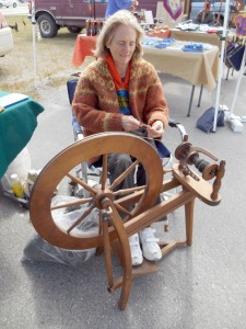 Martha Merry demonstrates spinning wool produced from the Lancashire Family Farm at the Soldotna Saturday Market. Lancashire Family Farm also sells raw and processed fleeces at the market, as well as spun wool in a verity of natural and dyed colors.