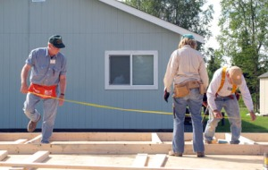 Photos by Ray Lee, for the Redoubt Reporter. Above and below, volunteers,  from the central Kenai Peninsula and from the Lower 48 with Habitat for Humanity's Care-A-Van program, work on a build site in Kenai last month. When finished, this will be Central Peninsula Habitat for Humanity's 18th home.