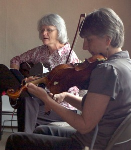 Photo by Ray Lee, for the Redoubt Reporter. The Kenai Fine Arts Center hosted a free concert at noon Monday to kick off the Kenai Peninsula Orchestra's Summer Music Festival. Here, Barb Anderson maintains a melodic strum as Sue Biggs improvises on her violin. Concerts continue this week and next.