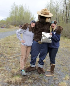 Kristin Fuller, left, and Kristine Route, right, with AmeriCorps, show off a Pack It Out bag  with Smokey the bear.