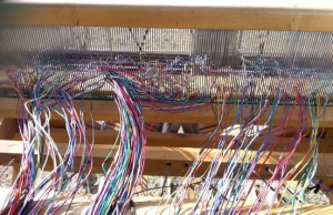 Photos courtesy of Keren Lowell. Above, electronic wire twists and snarls in a loom, but eventually (below) straightens out to become the warp of a woven art piece.