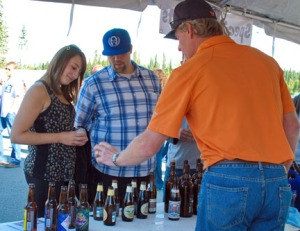 Photo courtesy of Elaine Howell. Gene Diamond from Specialty Imports in Anchorage discusses the beer choices available to Leah Swan and Josh Allison, both of Soldotna.