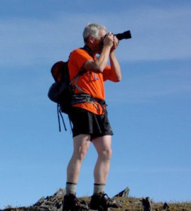 Photo courtesy of Mike Crawford. Clark Fair lines up a photo while on a mountain hike.  Being on the business end of a camera is a common view of Fair.